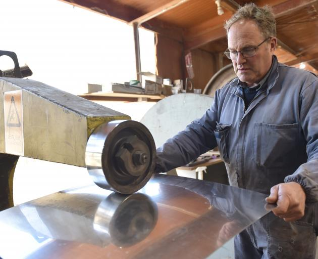 Rod Tempero works a piece of aluminium on a wheeling machine.