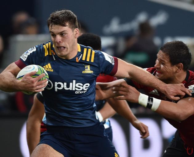 Highlanders flanker Dillon Hunt brushes off the tackle of Crusaders loose forward Whetu Douglas...
