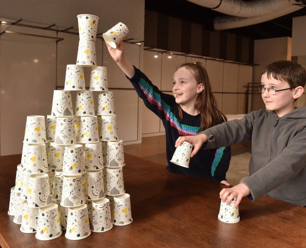 Kyla Rae (9) and her brother Toby (8) try to add to a structure they have built from paper cups...