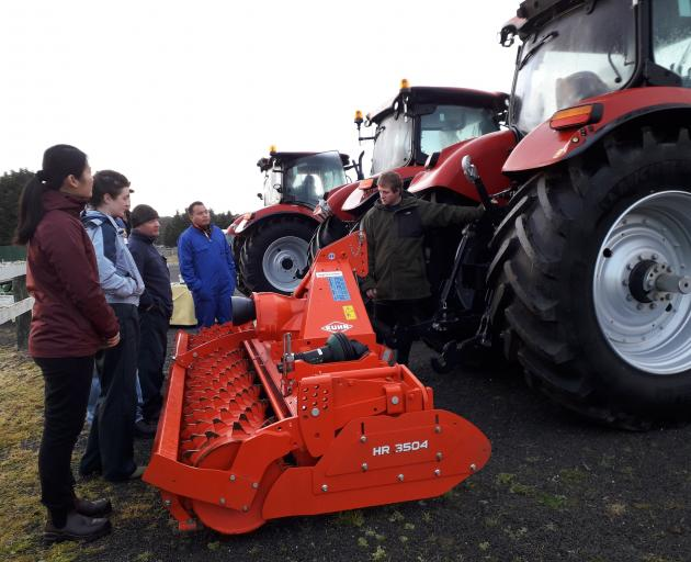 Students listen to tutor David Toole (right) discussing rural contracting equipment during a...