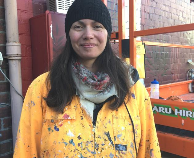 Aroha Novak braved cold weather to paint the mural. Photo: Chris Tobin