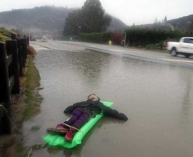 A floating dummy tethered to a fence next to the floodwaters on Aubrey Rd amused drivers and...