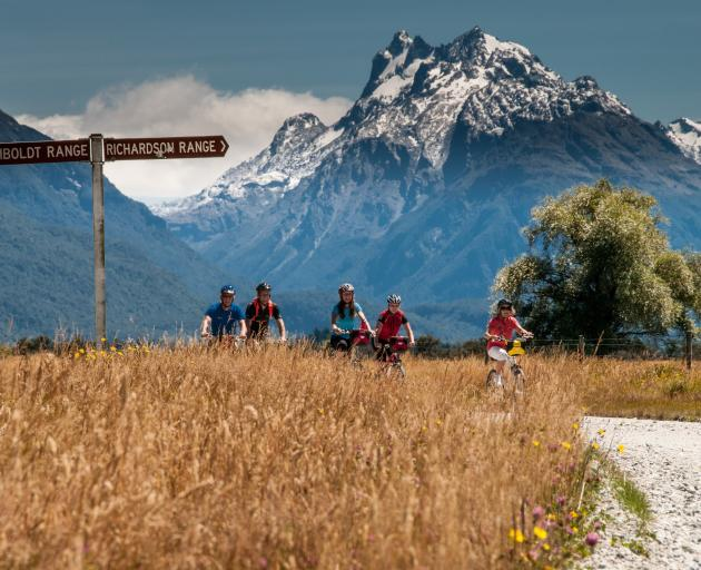 Cosmos Peak towers over cyclists en route to Paradise. PHOTO: LAURENCE BELCHER/PARADISE PICTURES