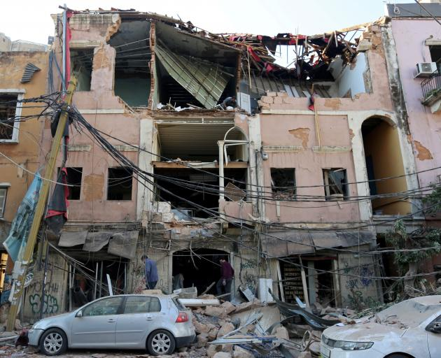 Men inspect a damaged building near the site of Tuesday's blast in Beirut's port area. Photo:...