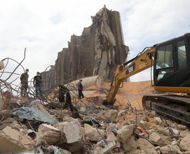 An excavator cleans debris near the damaged grain silo at the site of the blast at Beirut's port...