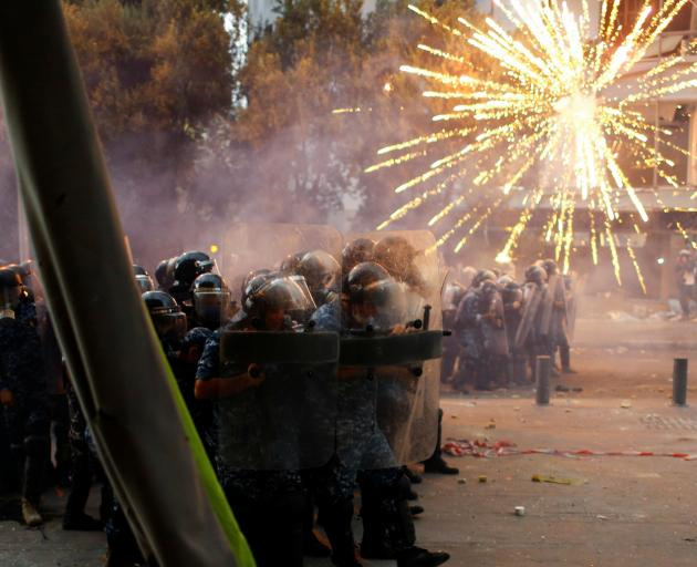 Fireworks are set off in front of police as anti-government protests continued in Beirut on...