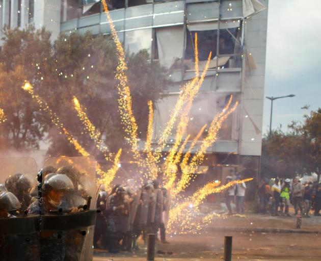 Fireworks are set off in front of police officers during anti-government protests that have been ignited by a massive explosion in Beirut. Photo: Reuters