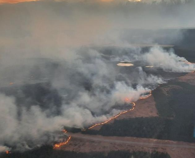 The fire near Twizel burns on both sides of the road yesterday. Photo: Aerial crews via Mackenzie District Council