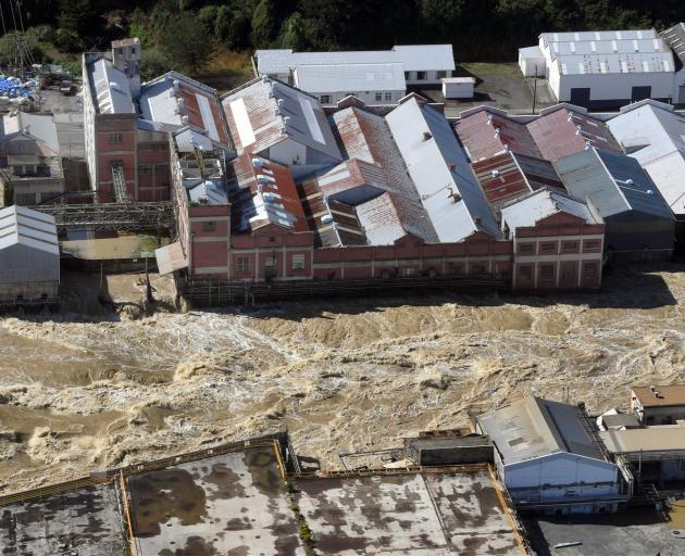 The flooded Mataura River rips past the former Mataura paper mill. Photo: Stephen Jaquiery