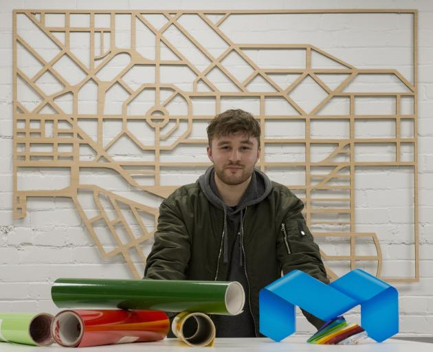 Miller Studios production manager Oliver Kloogh, who is standing in front of a map of Dunedin...