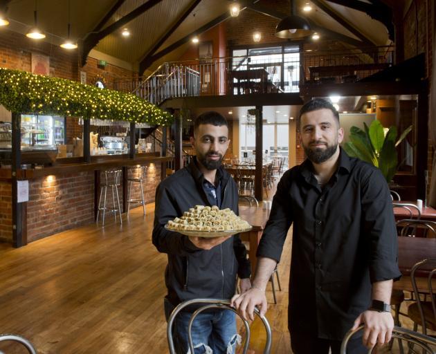 Al Sultan restaurant owner Mohammad Saad Aldeen holds some baklava while standing alongside his...
