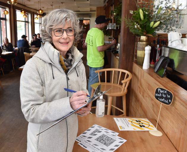 St Clair resident Melanie Garthwaite signs into the Esplanade Restaurant on Thursday afternoon....