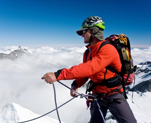 Paul Hersey belays (secures) another climber on a glacier between Mt Walter and Mt Green in...