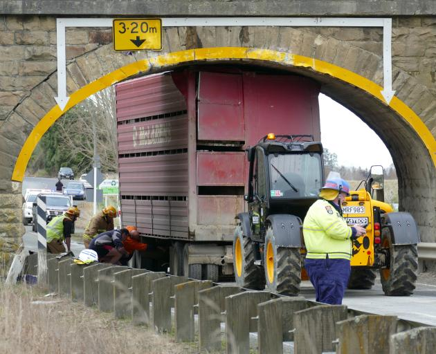 Emergency services work to dislodge a stock truck carrying cattle from beneath a railway bridge...