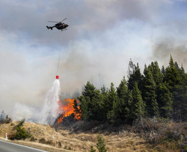 A helicopter dumps the contents of a monsoon bucket on the fire burning out of control in the...