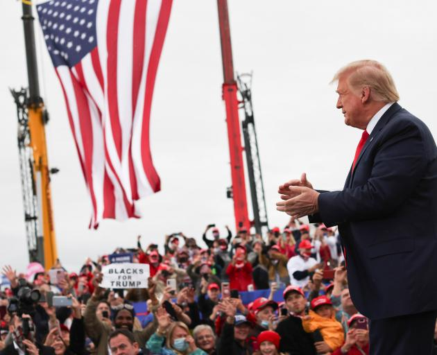 President Donald Trump acknowledges the crowd at MBS International Airport in Freeland, Michigan....