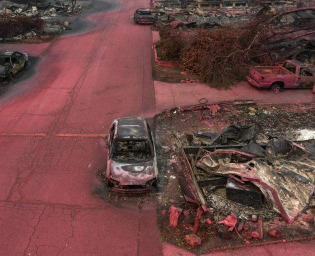 Red fire retardant blankets burned residences and vehicles in the aftermath of the Almeda fire in...