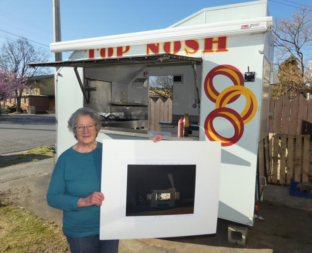 Jean Bonsor in her Top Nosh food trailer holds a signed copy of Grahame Sydney's eponymous work....