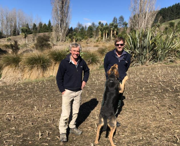 Peter Evans and son John stand beside one of their fenced off wetland areas, where they plant and...
