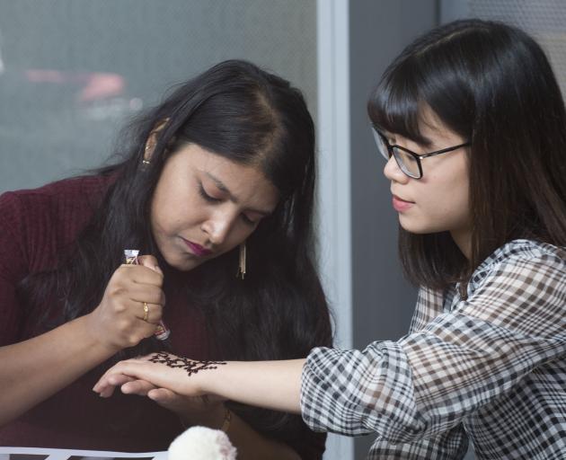 Keerthana Ram (23), of Chennai, India, gives a henna tattoo to Mally Ha (25), of Ho Chi Minh City...