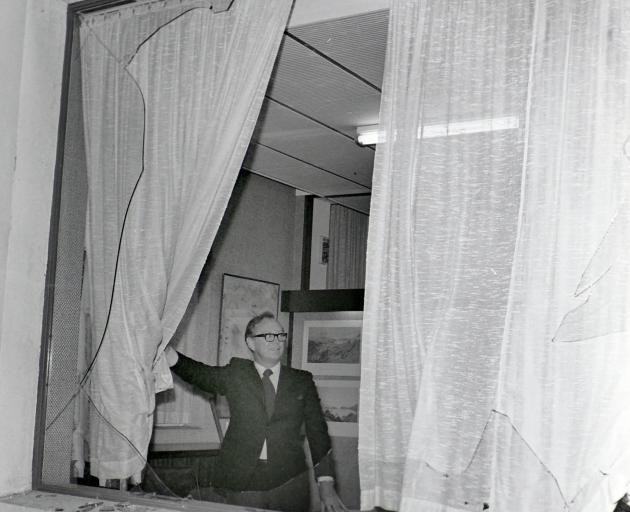 Mr Bill McIndoe pulls back the curtain to survey the smashed plate glass window of his firm's...
