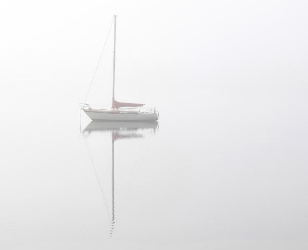 A yacht sits anchored in the fog off Grassy Point  by  Portobello Rd yesterday. Photo: Stephen...