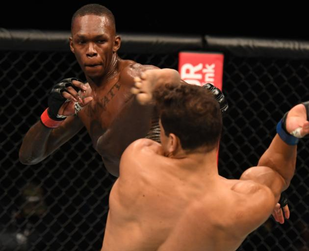 Israel Adesanya lands a kick to the head of Paulo Costa. Photo: Getty Images