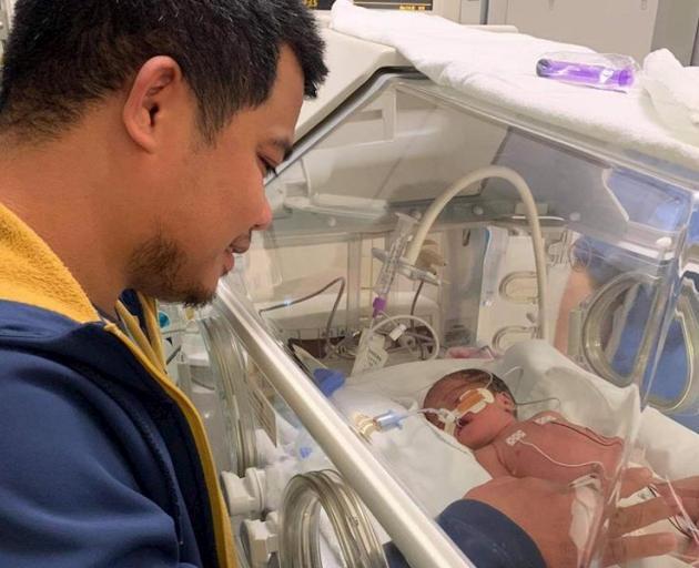 Heylon Sevilla, with son Nio (5), keeps a watchful eye on newborn daughter Estella Marie while he...