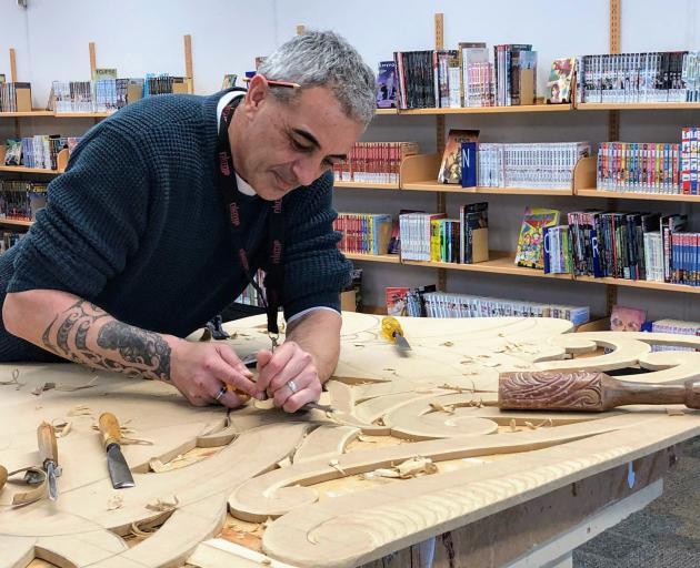 Carver Greg Houkamau works on a piece which represents the Maori legend of Tane seeking Nga Kete...