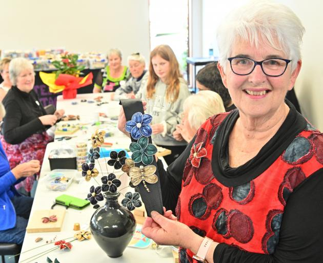 Tutor Jan Letts displays some of the brooches that were made out of recycled coffee pods during...