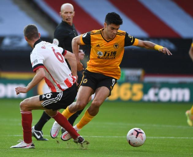 Raul Jimenez of Wolverhampton Wanderers attacks as Chris Basham of Sheffield United tries to stop...