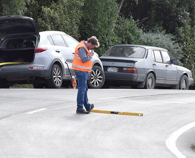 An investigator takes measurements at the scene of a fatal crash in Ravensbourne Rd, Dunedin,...