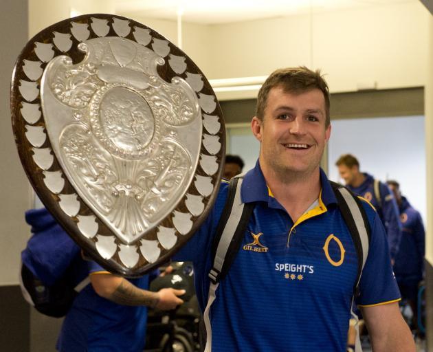Otago captain Michael Collins brings the Ranfurly Shield with him through Dunedin Airport...