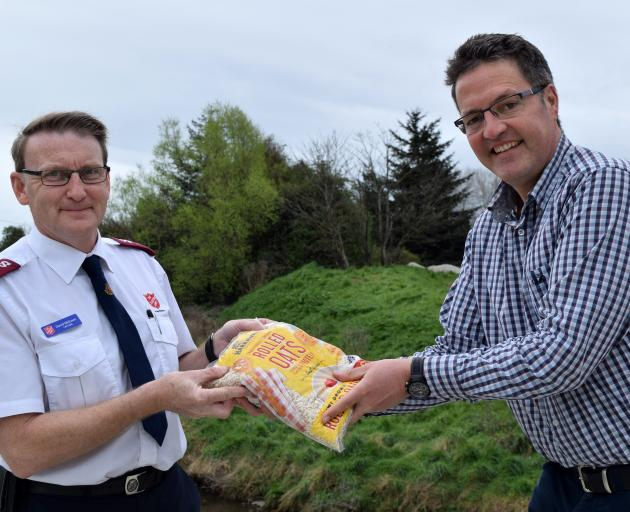 Salvation Army Dunedin City corps officer Dave McEwan (left) receives a bag of oats from Harraway...