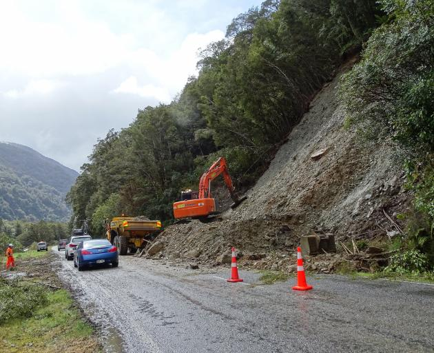 Road crews continued to clear away mud from the slip at Burke Flat as the first cars drove north...