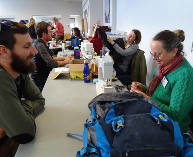 Dave Stewart, of Hawea Flat, watches Ros Goulding, from Deep Canyon, sew a tear in his backpack...