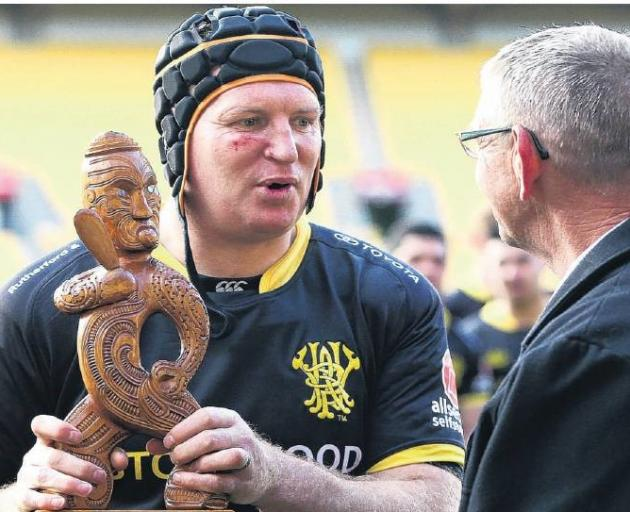 Wellington captain Thomas Waldrom accepts the Mike Gibson MemorialTrophy from Guy Gibson after...