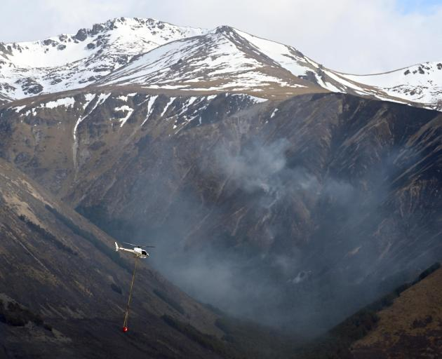 A helicopter heading to fight the Ohau fire passes a burnt-out gully on Monday. Researchers say...