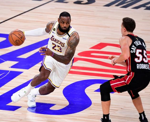 Los Angeles Lakers star LeBron James drives at Miami Heat guard Duncan Robinson during Monday's...