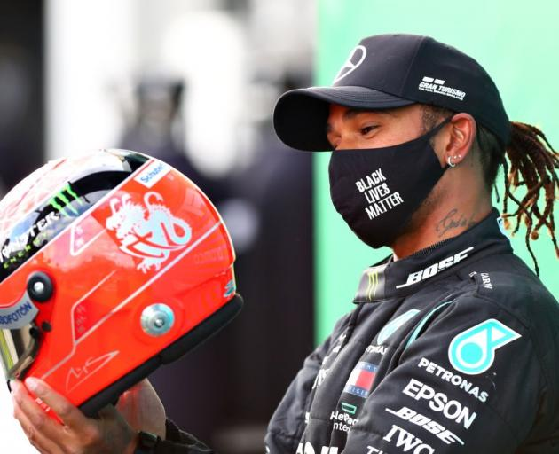 Lewis Hamilton is presented with a helmet of Michael Schumacher's as he ties his record for most...