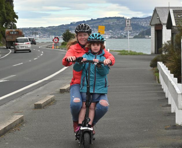 Lucy Goldsmith rides her electric scooter with daughter Freya Lester (6) on the Vauxhall to...