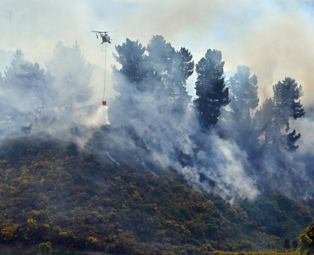 A helicopter drops water on to a gorse fire off State Highway 1, near Waikouaiti, yesterday....