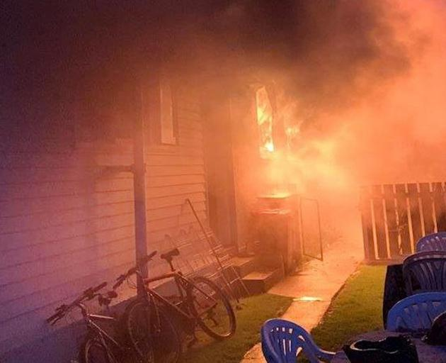 Flames and smoke pour out of the Fashwal family's house in Oban St, Mosgiel, during a blaze that...