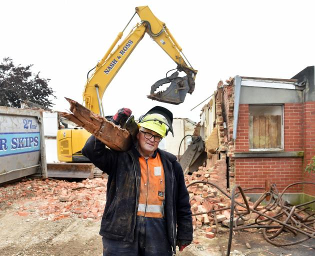 Builder and engineer Peter Mason, of Dunedin, carries one of 20 beams he salvaged from the...
