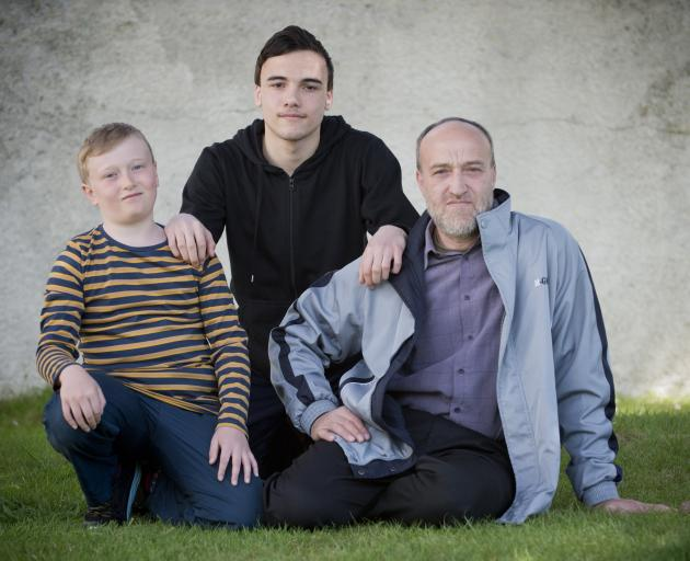 Fashwel family members (from left) Anas (10), Abdel Karim (16) and their father Walid are putting...