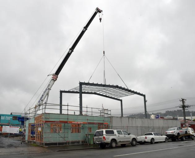 A crane supports a frame in place at a construction site in Ward St, Dunedin. Allied Pickfords...