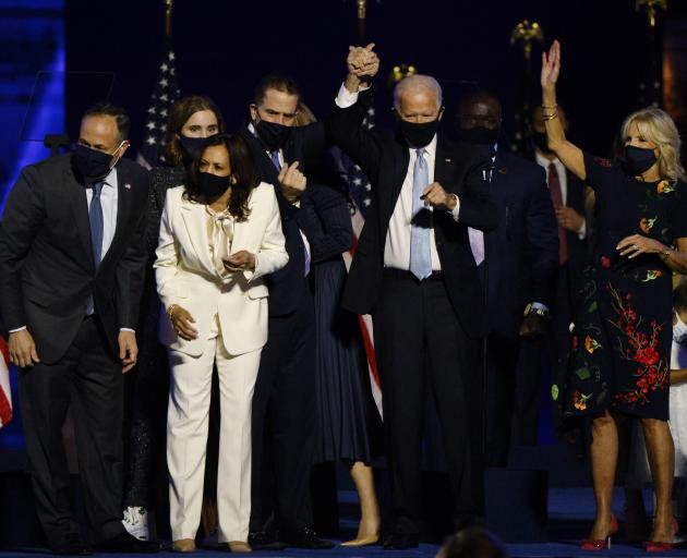 Joe Biden holds up his son Hunter's hand, as they and vice presidential nominee Kamala Harris and...