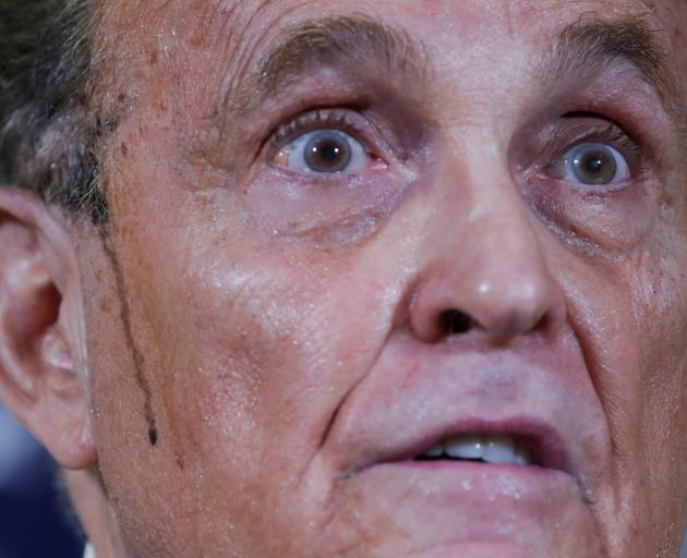 Rudy Giuliani, personal attorney to US President Donald Trump, speaks as sweat runs down his...