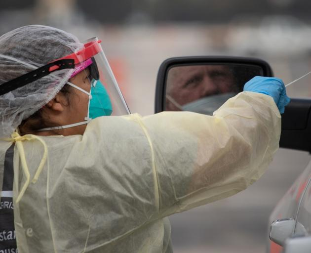 A healthcare worker prepares to swab a man at a Covid drive-thru testing location in Houston,...