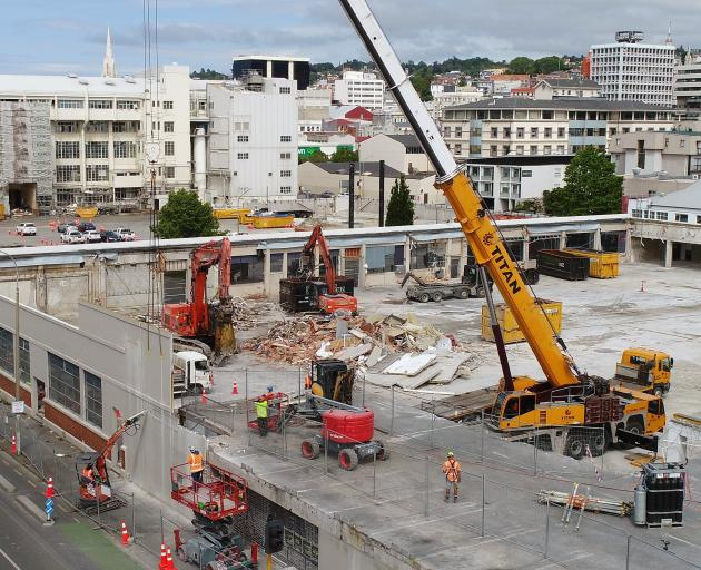 A crane is used to remove part of the former Wilson Parking building, which is being demolished...